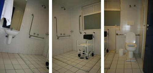 Pia, espelho, espaço do chuveiro com cadeira de banho e vaso sanitário