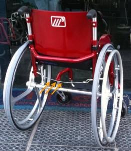 Cadeira M3 de costas com rodas de liga leve. Setas indicam o cabo de aço usada para dobrar a cadeira.