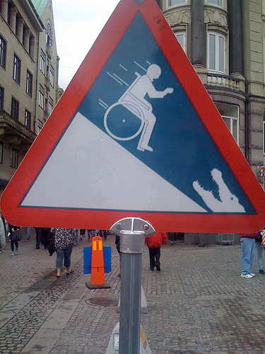 placa mostrando um cadeirante descendo uma ladeira com um jacaré no final dela