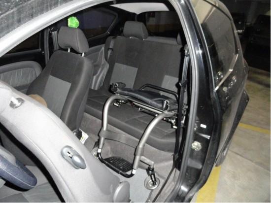 cadeira rígida acomodada no banco traseiro de um carro compacto
