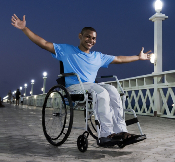 Rapaz sentado numa cadeira de rodas com sorriso no rosto e os braços abertos.